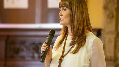 Eine Frau spricht in ein schwarzes Mikrofon