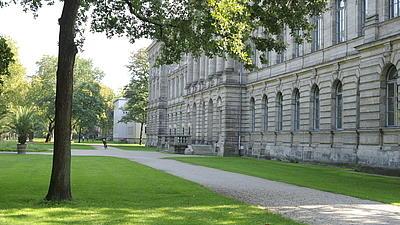 Ein großes altes Gebäude neben einem Park mit Wegen, Rasen und Laubbäumen. Im Hintergrund ist ein anderes helles Gebäude zu erkennen, ein Radfahrer und verschiedene Personen.