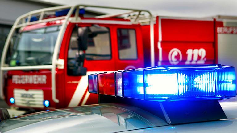 Detailaufnahme von einem Blaulicht auf einem Fahrzeugdach, welches leuchtet. Im Hintergrund erkennt man ein großes rotes Löschgruppenfahrzeug.