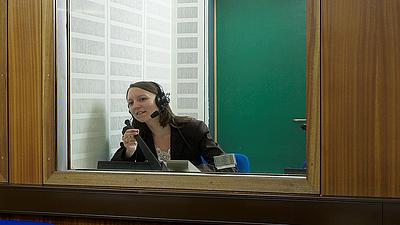 Eine Dolmetscherin in einer Dolmetscherkabine.