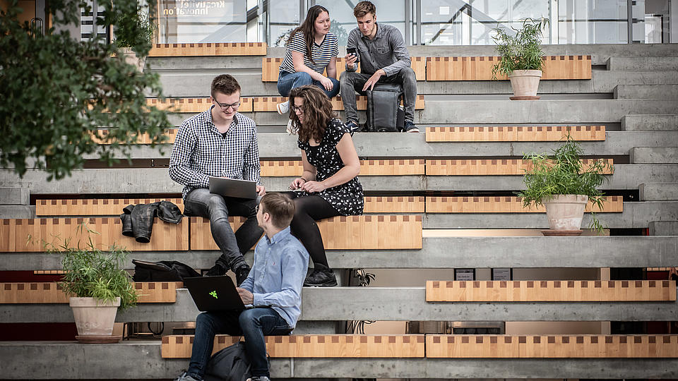 Studenten sitzen auf Treppenstufen mit Laptops und unterhalten sich.