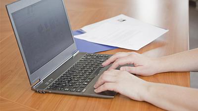 Ein Laptop steht aufgeklappt auf einem Holztisch, die Hände einer Person arbeiten auf dem Touchpad.