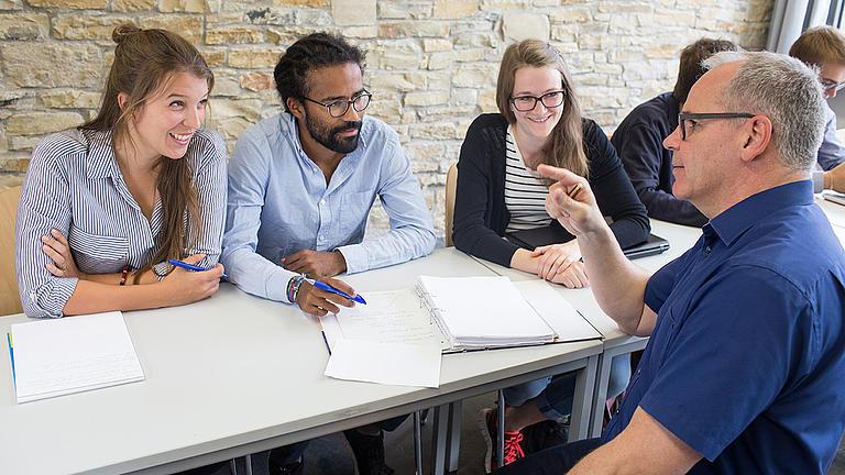 Ein Dozent erklärt einer Gruppe von Studierenden etwas.