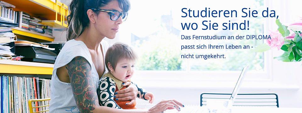 Eine Frau mit Kind auf dem Schoss sitzt vor einem Laptop.
