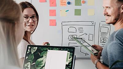 Zwei Studentinnen und ein Student an einer Tafel mit Post It's und Tablets in der Hand