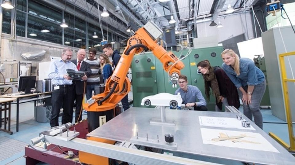 Maschinenbaustudenten mit automatischem Greifarm