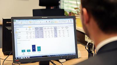 Ein Mann sitzt an einem Monitor und hat eine Kalkulation in der Ansicht
