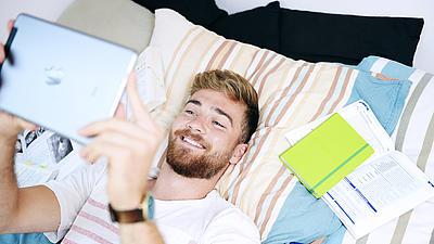 Student liegt mit Tablet und Büchern auf einem Bett