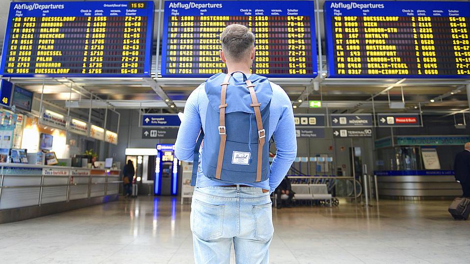 Ein junger Mann steht vor einer Abflugtafel am Flughafen.