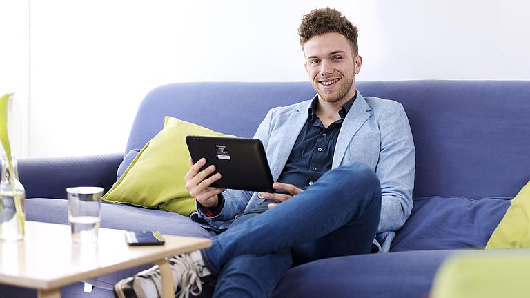 Ein junger Mann sitzt auf einer blauen Couch und hält ein Tablet in seinen Händen.