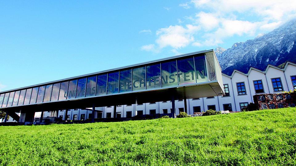 Außenansicht der Universität Liechtentein mit Bergen im Hintergrund blauem Himmel und grünem Gras im Vordergrund