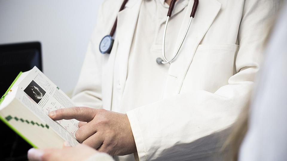 Ein Mann im weißen Kittel, mit Stethoskop um den Hals, zeigt einer anderen Person in einem Buch eine Textpassage.