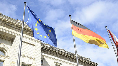 Die Europaflagge und die Deutschlandfahne wehen vor einem Gebäude.