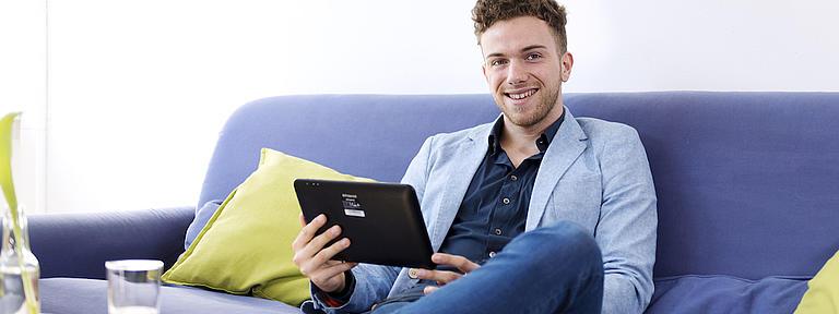 Ein junger Mann sitzt auf einer blauen Couch und hält ein Tablet in seinen Händen. Er hat ein Bein auf das andere gelegt und blickt lächelnd in die Kamera.