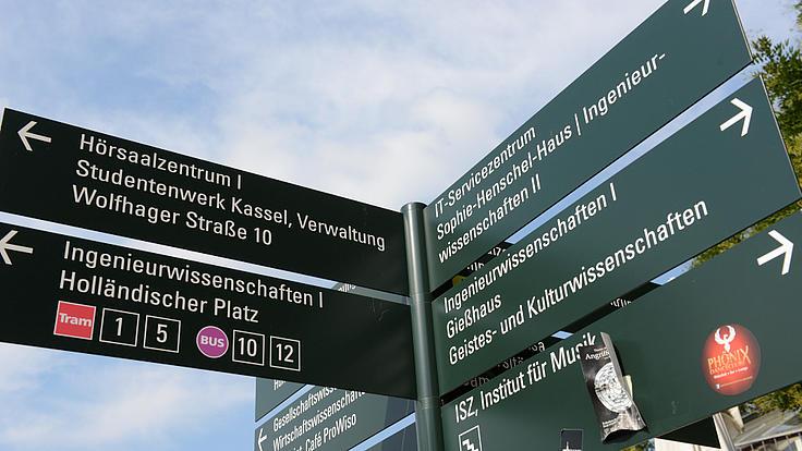 Grüne Wegweiser an der Uni Kassel.