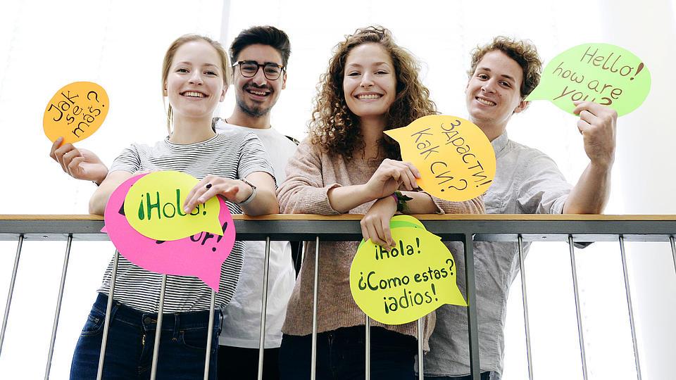 Vier junge Menschen stehen an einem Geländer und halten bunte Karten mit Grußworten in verschiedenen Sprachen hoch.
