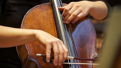 Nahaufnahme eines Cellos, das von einem Mann gehalten wird. Eine Hand hält einen Bogen über das Instrument. Die andere hält die Saiten fest.