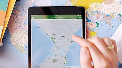 Eine Hand tippt auf eine Landkarte am Tablet.