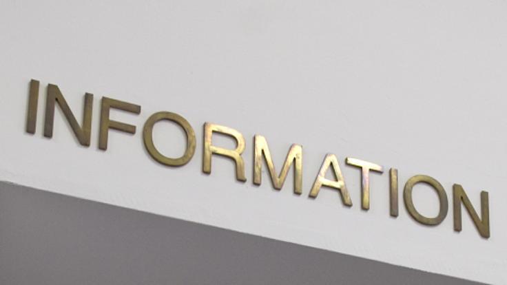Über einer Glastür steht in goldenen Buchstaben das Wort Information.