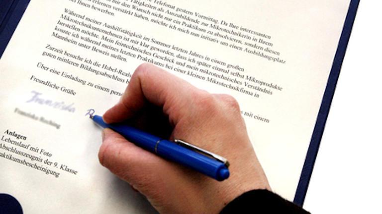Nahaufnahme eines Bewerbungsanschreibens in einer Mappe, eine Hand hält einen blauen Kugelschreiber und unterschreibt gerade das ausgedruckte Schriftstück.