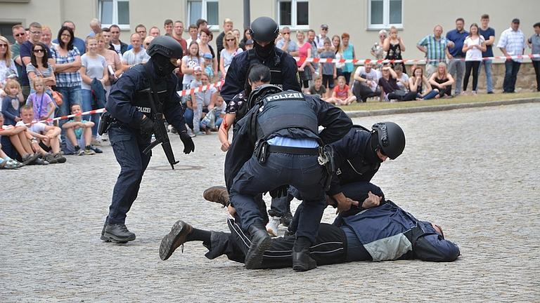 Polizisten nehmen bei einer Übung vor Publikum eine Person fest.