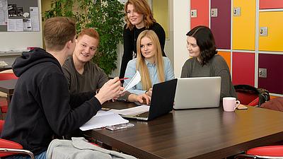 Studenten sitzend an einem Tisch und sich unterhaltend. Auf dem Tisch stehen zwei Laptops.