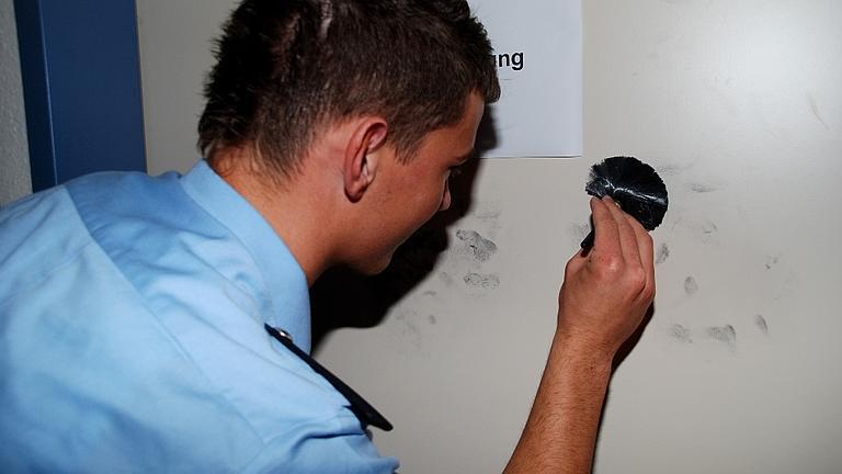 Ein Polizeischüler untersucht Fingerabdrücke.