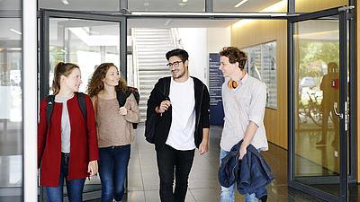 Zwei junge Frauen und zwei junge Männer stehen nebeneinander in einer gläsernen Eingangstür. Alle vier lächeln sich an.