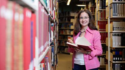 Eine Studentin liest ein Buch in einer Bibliothek.