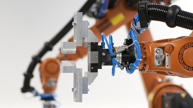 Ein orangefarbener Roboterarm mit silbergrauer Halterung.
