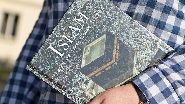 Nahaufnahme eines Buches über den Islam, welches sich eine Person unter den linken Arm geklemmt hat.