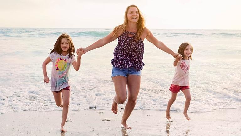Eine Frau mit zwei Kindern am Strand. Im HIntergrund das Meer.