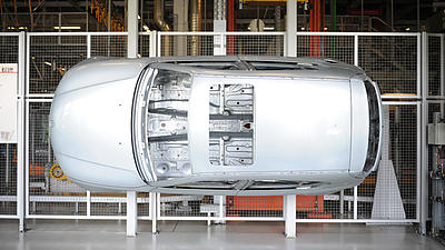 Die silberne Karosserie eines Automobils wurde zur Veranschaulichung mit dem Unterboden an ein Absperrgitter in einer Werkhalle montiert.