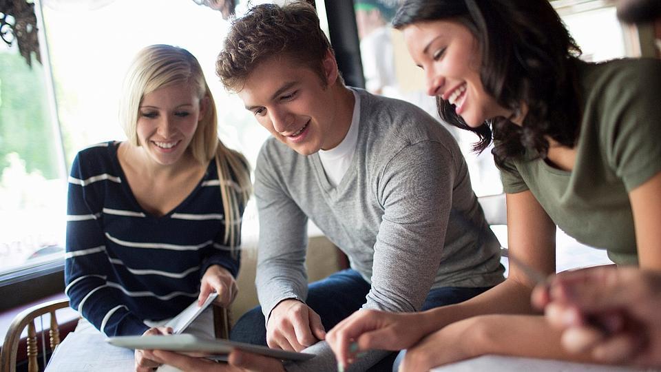 drei Menschen lesen im Tablet