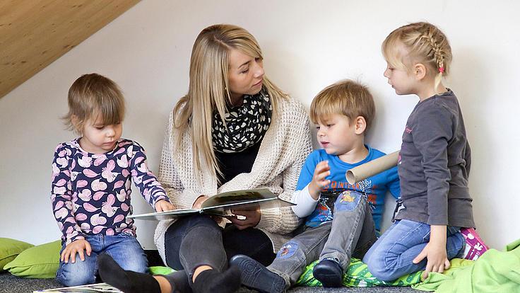 Eine Frau liest mit drei Kindern ein Buch.
