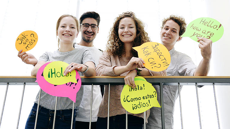 Four young people are showing colourful cards with greetings in different languages on them.