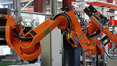 Ein großer oranger Roboterarm steht in einer Werkhalle
