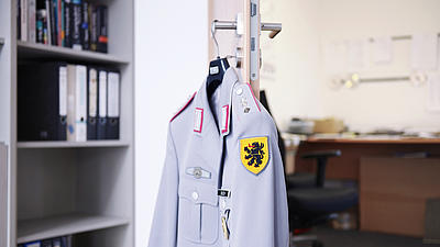 Blick auf eine graue Uniform der Bundeswehr, die an einem Türgriff hängt.