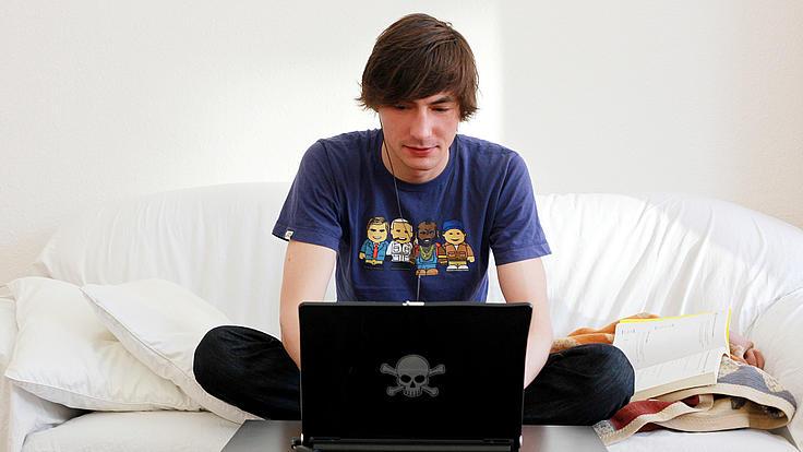 Ein Student sitzt auf seiner COuch und lernt am Laptop.