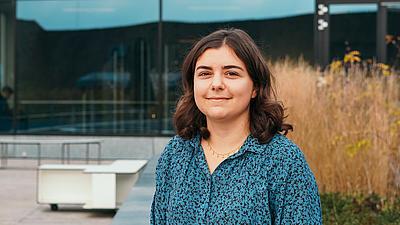 Bild einer dunkelhaaringen Studentin mit mittellangen offenen Haaren