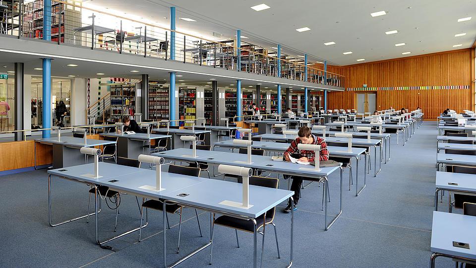 Ein Biblotheksraum mit Tischen und Stühlen und einem sitzenden Studenten, der in einem Buch stöbert.