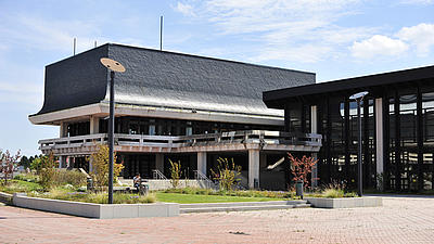 Ein Gebäude mit Flachdach und mit Spiegelglas verkleideter Fensterfront mit einem Anbau verkleidet mit Schiefer. Auf einem gepflastertem Innenhof neben einer Treppenanlage ist eine Grünfläche angelegt.