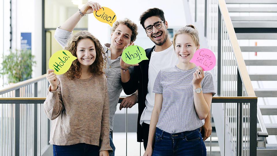 Vier junge Menschen zeigen Sprechblasen.Schilder. Auf diesen ist in vier Fremdsprachen das Wort Hallo zu lesen.