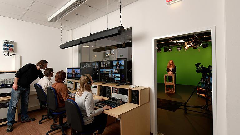 Studenten sitzend an PC. Ein Dozent zeigt etwas auf dem PC.