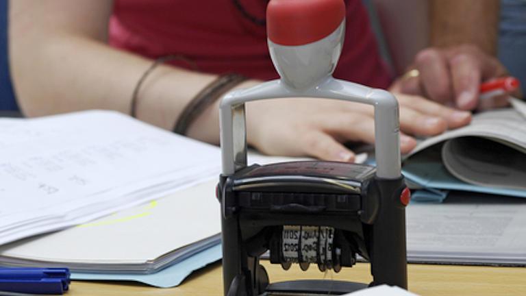 Ein Stempel auf einem Schreibtisch. Im Hintergrund sitzt eine Frau und faltet eine Akte auf.