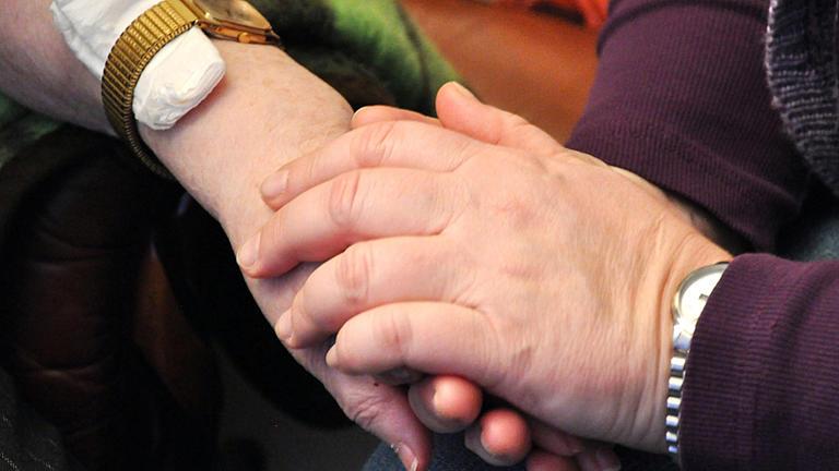 Eine männliche Hand umschließt eine weibliche Hand