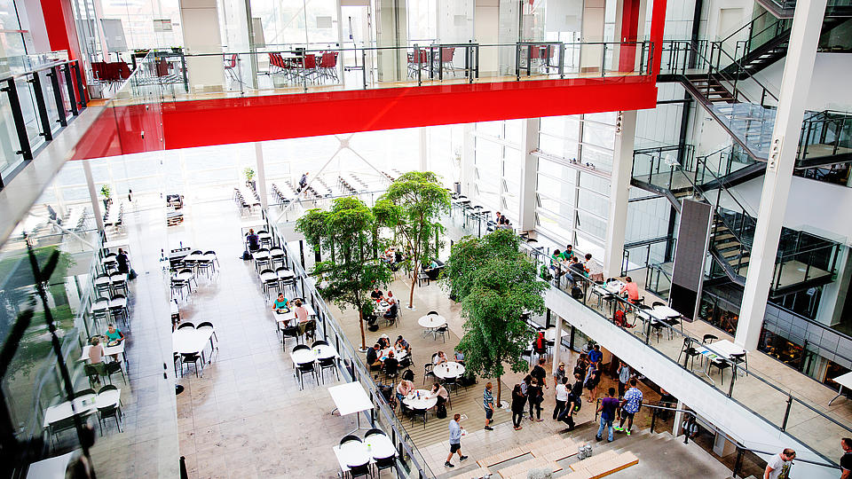 Der Eingangsbereich in rot und weiß der Universität Dänemark mit Tischen und Studenten.