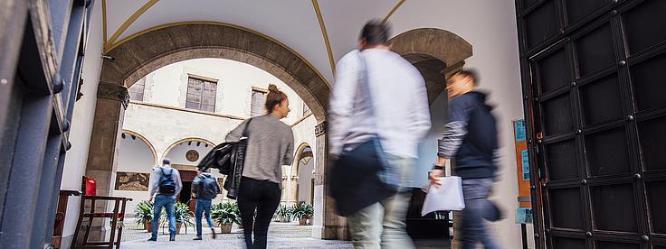 Studierende laufen durch den Innenhof der Akademie