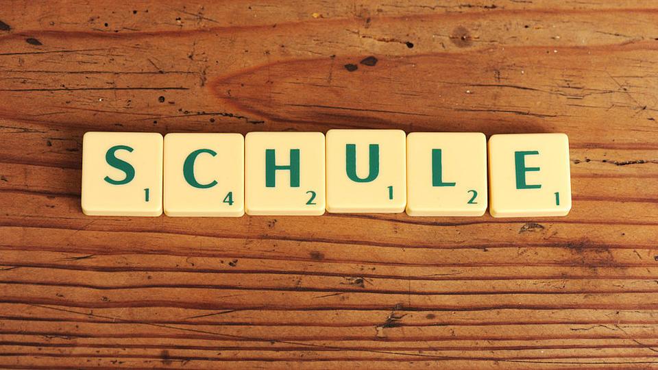 Auf einer rustikalen Holzoberfläche liegen sechs quadratische Spielsteine, jeweils mit einem grünen Buchstaben und einer Zahl bedruckt, die das Wort