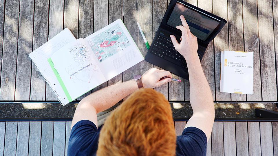 Ein Studierender sitzt mit Laptop auf einer Bank.